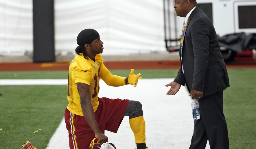 Washington Redskins quarterback Robert Griffin III talks with Tony Wyllie, the team's senior vice president for communications, after NFL football practice, Tuesday, Aug. 18, 2015, in Ashburn, Va. (AP Photo/Alex Brandon)