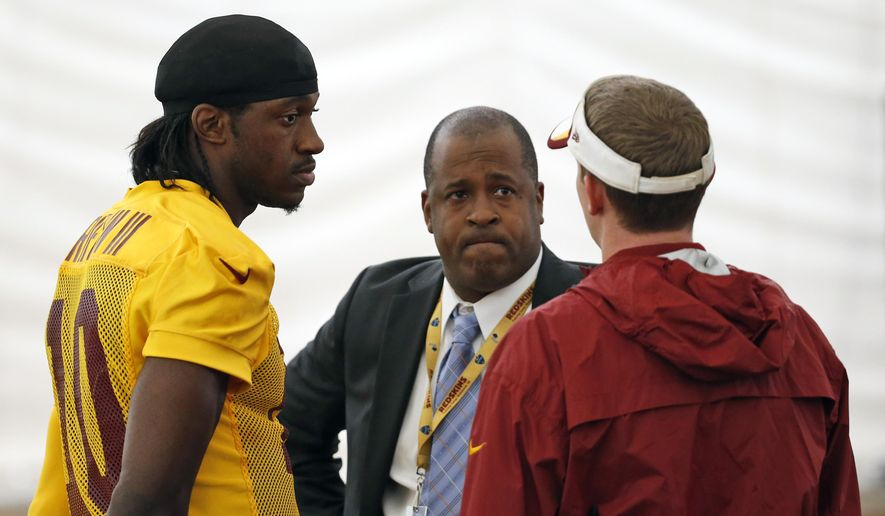 Washington Redskins quarterback Robert Griffin III, left, talks with Tony Wyllie, center, Redskins senior vice president for communications, and Ross Taylor, director of communications, after NFL football practice, Tuesday, Aug. 18, 2015, in Ashburn, Va. Griffin later spoke with reporters. (AP Photo/Alex Brandon) **FILE**