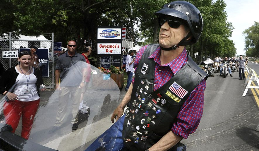 Illinois Gov. Bruce Rauner arrives on his motorcycle and greets supporters during a Governor's Day rally at the Illinois State Fair on Wednesday, Aug. 19, 2015, in Springfield, Ill. (AP Photo/Seth Perlman)
