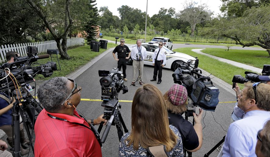Ron Spiller, director of code enforcement for Hillsborough County, center, behind microphones, addresses the media in front of where a sinkhole reopened, Wednesday, Aug. 19, 2015, in Seffner, Fla. The sinkhole reopened in the exact same location where one swallowed a man as he slept in his bed more than two years ago.  The new hole is 17 feet wide by 20 feet deep, according to Spiller.   (AP Photo/Chris O'Meara)