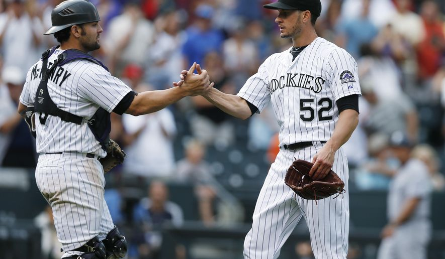 Colorado Rockies catcher Michael McKenry, left, congratulates starting pitcher Chris Rusin after Rusin retired San Diego Padres' Jedd Gyorko in the ninth inning of a baseball game Sunday, Aug. 16, 2015, in Denver. The Rockies won 5-0. (AP Photo/David Zalubowski)
