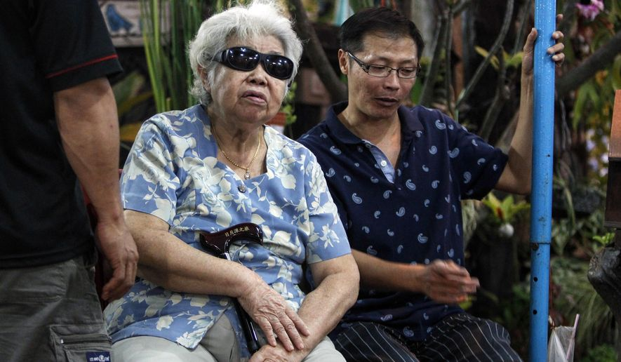 Goh Phaik Lan, 76, center, is accompanied by her son, Neoh Hock Lye, 44, as they prepare for the funeral of  Neoh Hock Guan's wife, Lim Saw Gaik, 49, and son, Neoh Jai Jun, 20, in Penang, Malaysia on Wednesday, Aug. 19, 2015. Both were killed in a bombing that killed a number of people at the Erawan shrine in downtown Bangkok, on Monday. (AP Photo/Joshua Paul)