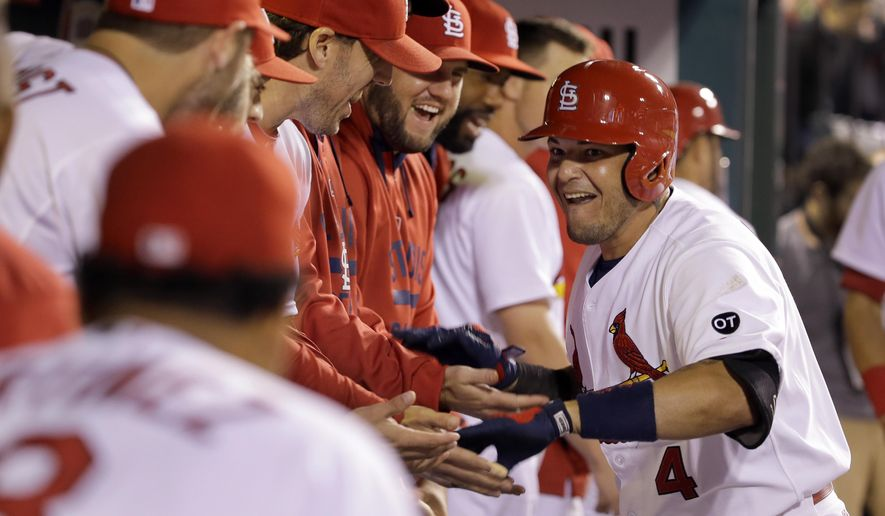 St. Louis Cardinals' Yadier Molina, right, is congratulated by teammates in the dugout after hitting a solo home run during the eighth inning of a baseball game against the San Francisco Giants, Wednesday, Aug. 19, 2015, in St. Louis. (AP Photo/Jeff Roberson)