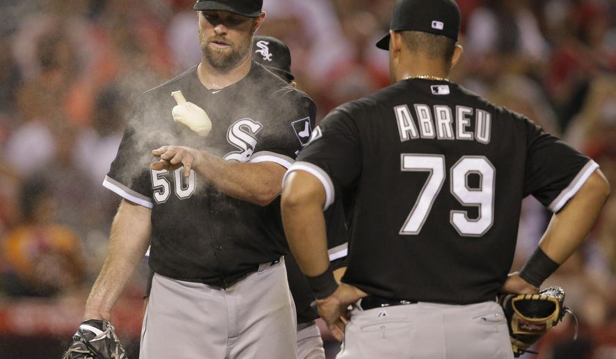 Chicago White Sox starting pitcher John Danks (50) tosses a rosin bag as he is approached by teammates, including first baseman Jose Abreu, during the seventh inning of a baseball game against the Los Angeles Angels, Tuesday, Aug. 18, 2015, in Anaheim, Calif. (AP Photo/Jae C. Hong)