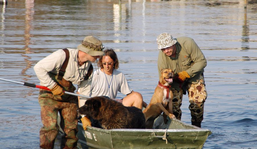 This Sept. 9, 2005 photo provided by Best Friends Animal Society shows a volunteer, center with Best Friends Animal Society rescue team members Ethan Gurney, left, and Jeff Popowich, right, retrieving dogs from the floods of Hurricane Katrina in New Orleans. Since the storm struck on Aug. 29, 2005, laws have changed how animal welfare groups and emergency responders approach pet rescues. They also have received training to better catalog rescued animals. (Troy Snow/Best Friends Animal Society via AP)