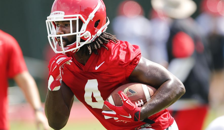 In this photo taken Aug. 4, 2015, Georgia running back Keith Marshall (4) carries the ball during  NCAA college football practice in Athens, Ga. Marshall's return to good health is a big reason Georgia believes it will have quality depth behind tailback Nick Chubb this season. Marshall hasn't been the same since running for 759 yards as a freshman in 2012.(AP Photo/John Bazemore)