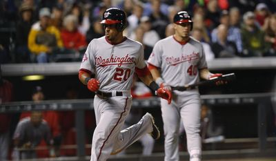 Washington Nationals' Ian Desmond scores from third base on a wild pitch thrown by Colorado Rockies starting pitcher David Hale during the fifth inning of a baseball game Tuesday, Aug. 18, 2015, in Denver. (AP Photo/David Zalubowski)