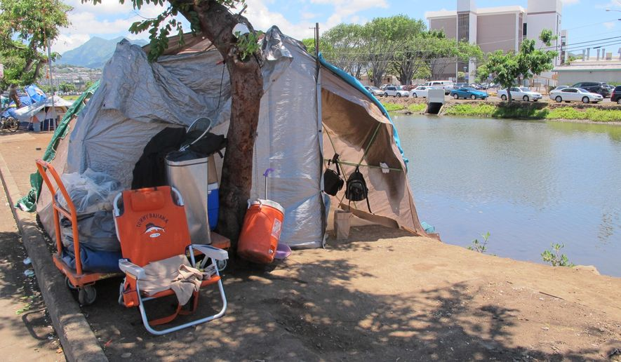 Tents and homemade structures line the banks of the Kapalama Canal on Wednesday, Aug. 19, 2015 in Honolulu. Honolulu Mayor Kirk Caldwell signed a bill to ban camping along the banks of city-owned waterways including this canal, where homeless people are living. (AP Photo/Cathy Bussewitz)
