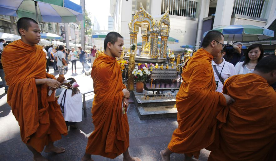 Buddhist monks walk at the Erawan Shrine, the site of the explosion, at Rajprasong intersection in Bangkok, Thailand, Wednesday, Aug. 19, 2015. The central Bangkok shrine reopened Wednesday after Monday's bomb blast to the public as authorities searched for a man seen in a grainy security video who they say was the prime suspect in an attack authorities called the worst in the country's history. (AP Photo/Sakchai Lalit)