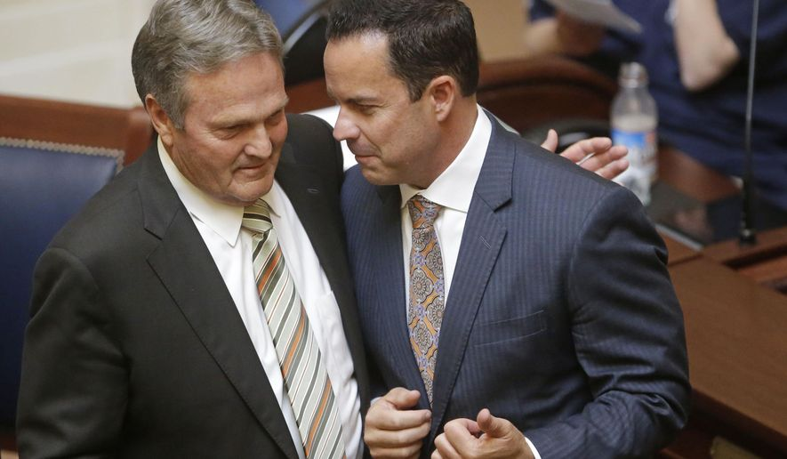 State Sen. Jerry Stevenson, R-Layton, left, and Rep. Brad R. Wilson, R-Kaysville, hug after Utah's Legislature signed off on a move to build a new state prison near Salt Lake City's airport during the Legislature's one-day special session Wednesday, Aug. 19,  2015, in Salt Lake City. (AP Photo/Rick Bowmer)