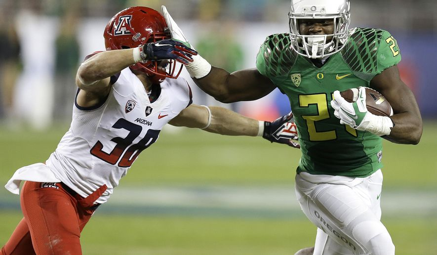 FILE - In this Dec. 5, 2014, file photo, Oregon's Royce Freeman, right, evades Arizona's Jared Tevis during the first half of a Pac-12 Conference championship NCAA college football game in Santa Clara, Calif. Just a sophomore, Freeman is already assuming a leadership role on the Ducks' offense. (AP Photo/Ben Margot, file)