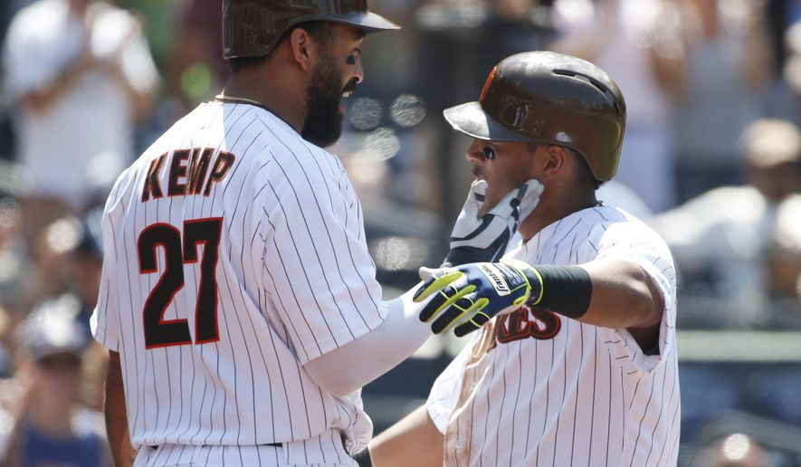 San Diego Padres' Yangervis Solarte gets a congratulatory slap from Matt Kemp, left, after his home run against the Atlanta Braves during the sixth inning of a baseball game Wednesday, Aug. 19, 2015, in San Diego. (AP Photo/Lenny Ignelzi)
