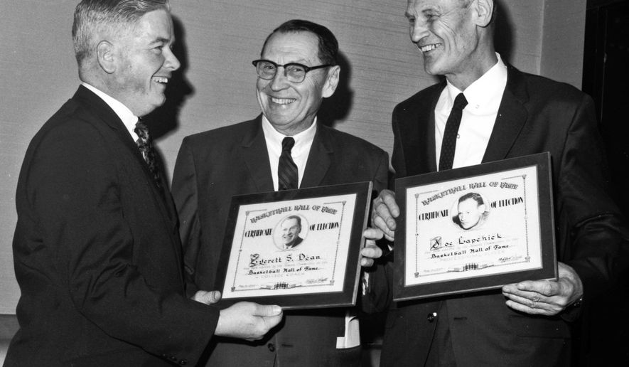 FILE - In this March 12, 1967, file photo, Bernie Beglane, left, president of the Metropolitan Basketball Writers Association, presents certificates to former Stanford coach Everett Dean, center, and former St. Johns coach Joe Lapchick during the association's annual dinner in New York. Beglane, a sports writer for 25 years, a freelancer for The Associated Press for almost 60 years, and an academic dean who founded the Athletic Administration program at St. John's, died Wednesday, Aug. 19, 2015, after a long illness. He was 88. (AP Photo/File)