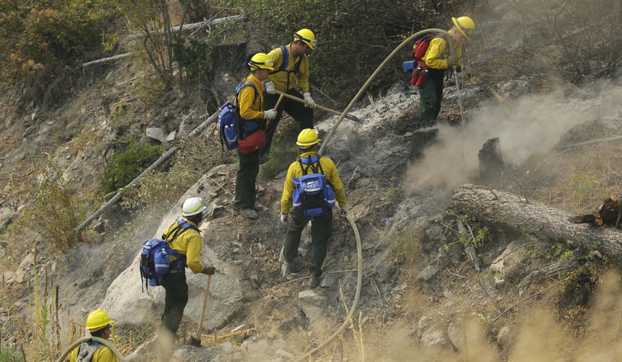 Firefighters and Washington National Guard soldiers work to extinguish hot spots on a hillside as they fight the First Creek Fire, Wednesday, Aug. 19, 2015, near Chelan, Wash. Firefighters braced Wednesday for high winds and heat that could fuel wildfires that have evacuated towns and destroyed houses in Washington state. (AP Photo/Ted S. Warren)