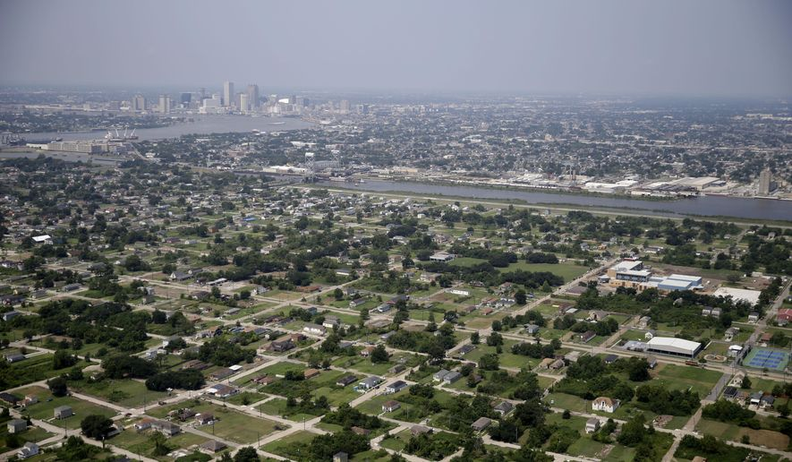 ADVANCE FOR USE FRIDAY, AUG. 21, 2015 AND THEREAFTER - This July 29, 2015 aerial photo shows empty lots and mostly new buildings in the Lower 9th Ward section of New Orleans, foreground. Ten years after Katrina, New Orleans remains a work in progress, aiming to reverse historic racial and economic injustices. (AP Photo/Gerald Herbert)
