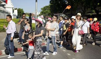 Chinese tourists cross the street in front of the Grand Palace in Bangkok, Thailand, Wednesday, Aug. 19, 2015. The bomb blast that ripped through a Bangkok shrine, leaving scores of casualties, may take a toll on  the country's tourism industry, the one bright spot in Thailand's blighted economy. (AP Photo/Penny Yi Wang)