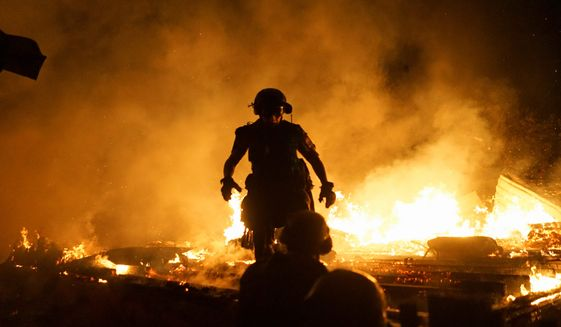 Firefighters were unable to save a house during shelling Monday night in Donetsk, Ukraine. The artillery exchange between government troops and Russia-backed rebels killed several people. (Associated Press)