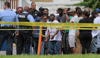 People confront police at the scene of a fatal officer-involved shooting at Walton Avenue and Page Boulevard on Wednesday, Aug. 19, 2015 in St. Louis. An armed man fleeing from officers serving a search warrant at a home in a crime-troubled section of north St. Louis was shot and killed Wednesday by police after he pointed a gun at them, the police chief said. (David Carson/St. Louis Post-Dispatch via AP)  EDWARDSVILLE INTELLIGENCER OUT; THE ALTON TELEGRAPH OUT; MANDATORY CREDIT