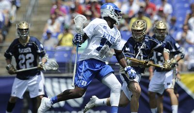 Duke's Myles Jones, left is pressured by Notre Dame's Chris Prevoznik in the first half of an NCAA championship lacrosse game Monday, May 26, 2014, in Baltimore.(AP Photo/Gail Burton)