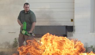 Ion Productions Team CEO Chris Byars demonstrates the XM42 he dubs the worlds' first commercially available handheld flamethrower on Tuesday Aug. 18, 2015 in Lake Orion, Mich. His is one of two Midwest companies that are selling personal flamethrowers on the Internet. Warren, Mich., Mayor Jim Fouts is trying to extinguish the use of the devices in his city, the state's third largest. (Ryan Garza/Detroit Free Press via AP)