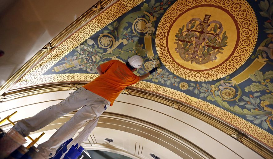 In this Aug.18, 2015 photo, an artist from Conrad Schmitt Studios uses decorative painting to repair deteroration to a mural in the House chambers as restoration of the Minnesota State Capitol continues in St. Paul, Minn. Renovators planned to spend $4.5 million on furniture and decorative finishing touches on the inside until House Republicans quietly pushed to bump up the furnishings allocation by $2 million, or 45 percent. (AP Photo/Jim Mone)