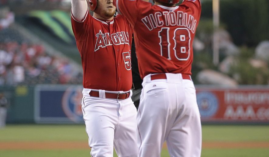 Los Angeles Angels' Kole Calhoun, left, celebrates his two-run home run with Shane Victorino during the first inning of a baseball game against the Chicago White Sox, Tuesday, Aug. 18, 2015, in Anaheim, Calif. (AP Photo/Jae C. Hong)
