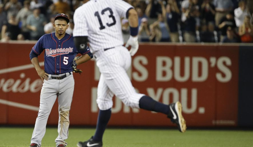 Minnesota Twins' Eduardo Escobar (5) watches as New York Yankees' Alex Rodriguez (13) runs the bases after hitting a grand slam during the seventh inning of a baseball game Tuesday, Aug. 18, 2015, in New York. (AP Photo/Frank Franklin II)