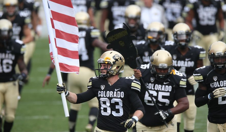 "FILE - In this Nov. 1, 2014, file photo, Colorado wide receiver Wesley Christensen carries a U.S. flag as he leads teammates onto the field for an NCAA college football game against Washington in Boulder, Colo. Thanks to a later start to the season and an increasing need to add revenue-generating games, college football teams across the country will have fewer bye weeks this season _ some none at all. Football is the largest revenue producer in college athletics, so schools try to get in as many home games as possible. ""We picked up another game,"" said Colorado coach Mike MacIntyre, whose team opens the season Sept. 3 at Hawaii. ""We need to create some more revenue, so we get another home game, so it puts money in our budget and everything else as we're building our program."" (AP Photo/David Zalubowski, File)"
