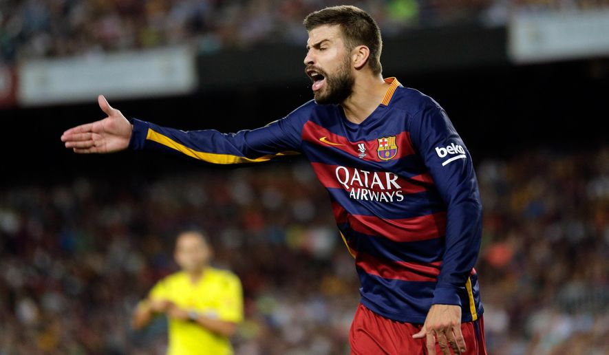 Barcelona's Gerard Pique gestures towards the linesman as referee  Velasco Carballo approaches to show him a red card during a second leg Spanish Super Cup soccer match between FC Barcelona and Athletic Bilbao at the Camp Nou stadium in Barcelona, Spain, Monday, Aug.17, 2015. (AP Photo/Manu Fernandez)