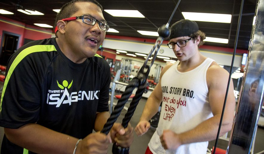 ADVANCE FOR FRIDAY AUG. 21 -In this Wednesday, Aug. 12, 2015 photo, Frank Brown works out with help from Tanner Bryan at SNAP Fitness in Roy, Utah. Frank Brown, who has a litany of health issues and devotes time to caring for his ailing father, is exactly the type of person who could have every excuse not to make losing weight a priority. But thanks to some new found friends, the 27-year-old Roy man has gained a lot more than a smaller waist at the gym. (Benjamin Zack/Standard-Examiner via AP) TV OUT; MANDATORY CREDIT