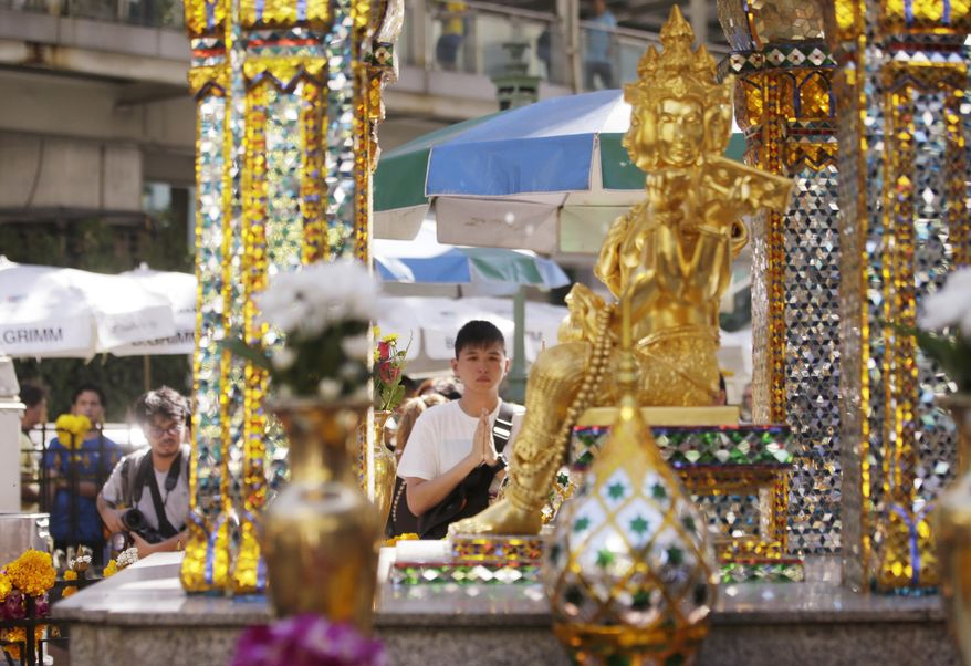 A man prays at the Erawan Shrine at Rajprasong intersection in Bangkok, Thailand, Wednesday, Aug. 19, 2015. The central Bangkok shrine reopened Wednesday after Monday's bomb blast to the public as authorities searched for a man seen in a grainy security video who they say was the prime suspect in an attack authorities called the worst in the country's history. (AP Photo/Sakchai Lalit)