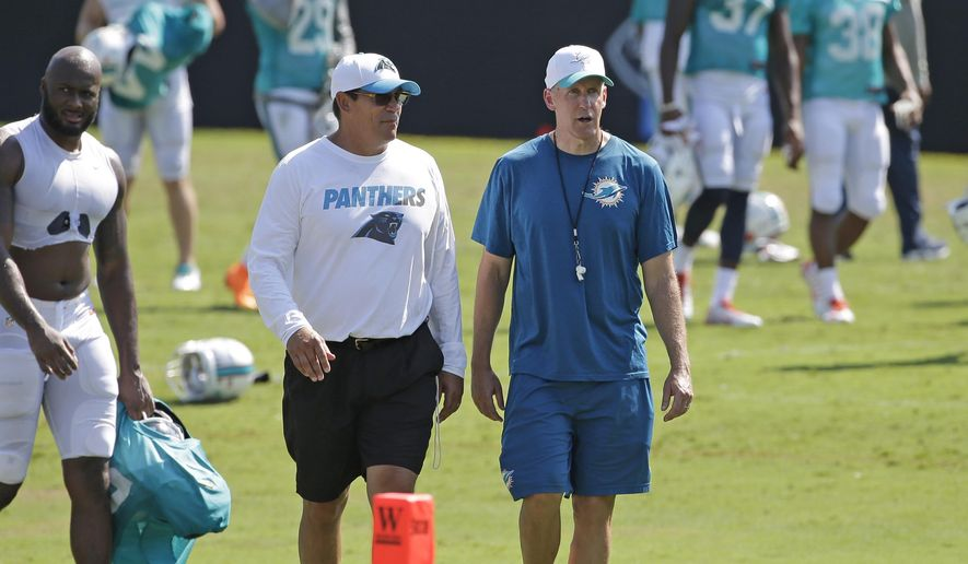 Carolina Panthers head coach Ron Rivera, left, and Miami Dolphins head coach Joe Philbin, right, talk as they walk off the field after a joint practice at the Panthers' NFL football training camp in Spartanburg, S.C., Wednesday, Aug. 19, 2015. (AP Photo/Chuck Burton)