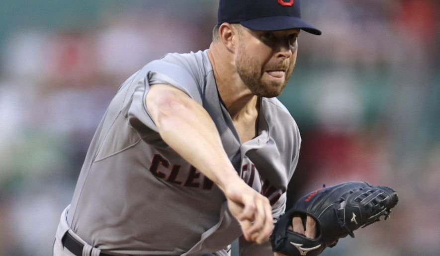 Cleveland Indians starting pitcher Corey Kluber delivers to the Boston Red Sox during the first inning of a baseball game at Fenway Park in Boston, Wednesday, Aug. 19, 2015. (AP Photo/Charles Krupa)