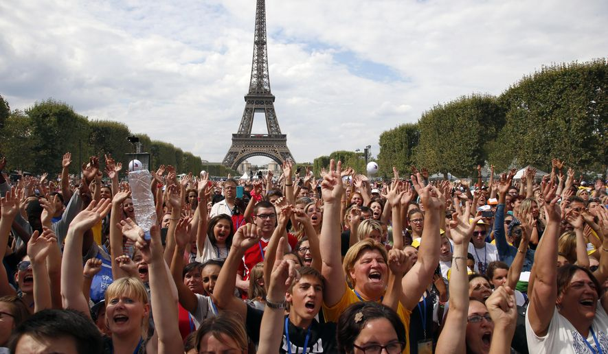 Children wave during a live music concert, the Vacation for Everyone day event, at the Eiffel Tower in Paris, France, Wednesday Aug. 19, 2015. The French charity Secours Populaire brought children from dozens of different countries, including those living through war, poverty or natural disasters, to join kids from France for a day of summer fun, allowing even those with limited means to take a vacation at the height of the French holiday season. (AP Photo/Francois Mori)