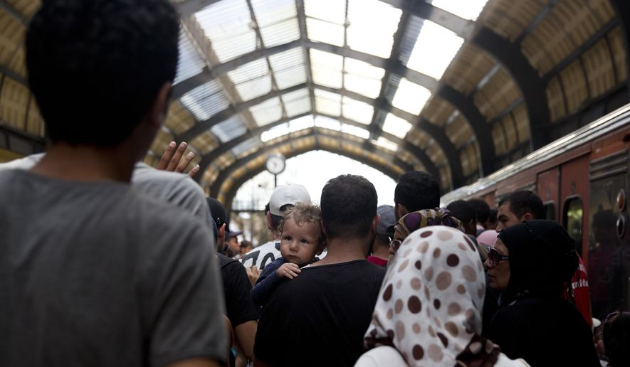 A young boy looks over his father's shoulder, as they head to a train after arriving on a ferry carrying about 2,500 migrants from Greek islands to Greece's main port of Piraeus near Athens, on Thursday, Aug. 20, 2015. Greece has been overwhelmed this year by record numbers of migrants arriving on its eastern Aegean islands, with more than 160,000 arriving since January. (AP Photo/Petros Giannakouris)