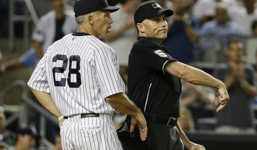 Home plate umpire Dan Iassogna ejects New York Yankees manager Joe Girardi during the ninth inning of the Yankees' baseball game against the Cleveland Indians, Thursday, Aug. 20, 2015, in New York. The Indians won 3-2. (AP Photo/Frank Franklin II)