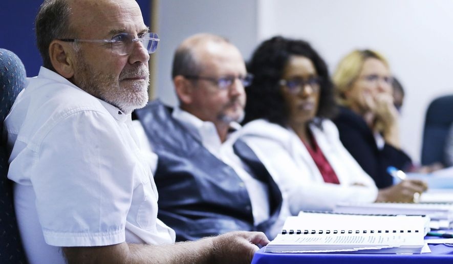 Tom Gillert, left, a member of the Oklahoma Pardon and Parole Board, listens to testimony along with other board members in the case of Benjamin Cole, who has been sentenced to die for killing his 9-month-old daughter in 2002, in Oklahoma City, Thursday, Aug. 20, 2015. The five-member board voted 3-2 against recommending that Gov. Mary Fallin grant clemency for 50-year-old Cole. (AP Photo/Sue Ogrocki)