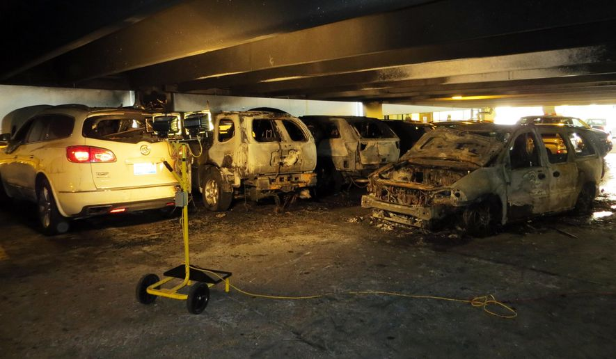 Several parked cars on the second level of the Taubman Parking Structure (P2) at 1600 East Medical Center Dr. in Ann Arbor, Mich., on Thursday, Aug. 20, 2015. Five vehicles were totaled and 5-7 more were damaged after a minivan moving through the structure engine started smoking and spread to the nearby vehicles. (Jack Walsworth/The Ann Arbor News via AP)