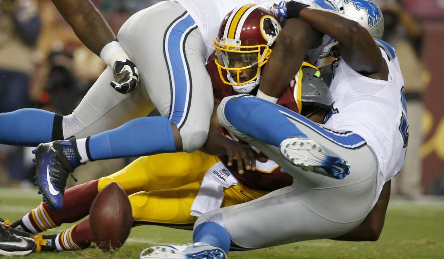 Washington Redskins quarterback Robert Griffin III fumbles the ball as he's sacked by Detroit Lions defensive end Tyrunn Walker, top, and defensive end Ezekiel Ansah, right, during the first half of an NFL preseason football game, Thursday, Aug. 20, 2015, in Landover, Md. (AP Photo/Alex Brandon)