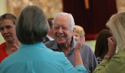 In this Sunday, Aug. 16, 2015, file photo, former President Jimmy Carter reaches to embrace his brother Billy's widow Sybil while greeting family following service at Maranatha Baptist Church in Plains, Ga. (Ben Gray/Atlanta Journal-Constitution via AP, File)