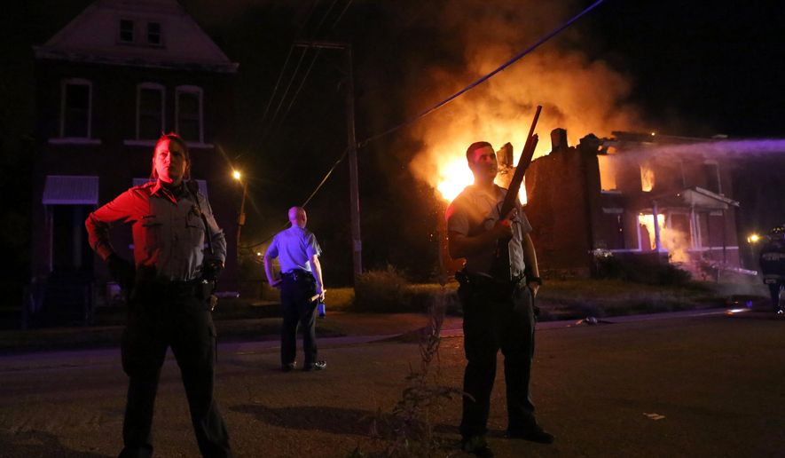 Police stand guard as firefighters extinguish a vacant house that was set on fire during protests following a fatal officer-involved shooting Wednesday, Aug. 19, 2015, in St. Louis. A black 18-year-old fleeing from officers serving a search warrant at a home in a crime-troubled section of St. Louis was fatally shot Wednesday by police after he pointed a gun at them, the city's police chief said. (Laurie Skrivan/St. Louis Post-Dispatch via AP)  EDWARDSVILLE INTELLIGENCER OUT; THE ALTON TELEGRAPH OUT; MANDATORY CREDIT