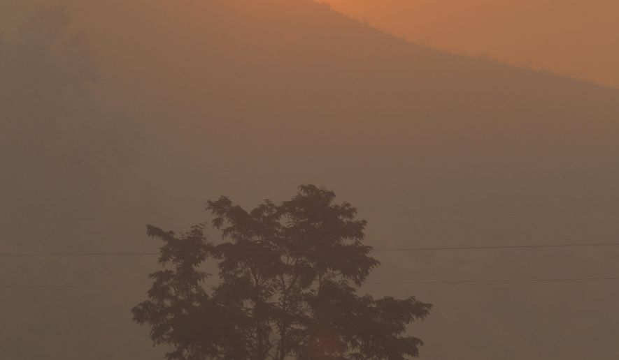 The sun rises in smokey air over a burnt-out ridge along Twisp River Road in Twisp, Wash. Thursday, Aug. 20, 2015, the day after three firefighters were killed fighting a wildfire near the town.  Firefighters on several fronts are fighting against raging wildfires advancing on towns in the north-central part of the state. (AP Photo/Ted S. Warren)