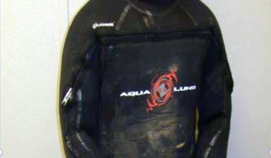 This April 25, 2015 photo, from the U.S. Border Patrol and introduced as evidence in U.S. District Court, Evelio Padilla, a Honduran national, in a wetsuit after his arrest for attempting to smuggle over 50 pounds of cocaine into the U.S. from Mexico by way of a partly-underwater tunnel that crossed the border into a canal near Calexico, Calif. Padilla pleaded guilty Wednesday, Aug. 19, in federal court in San Diego to one count of possession of drugs with intent to distribute. (U.S. Border Patrol via AP)
