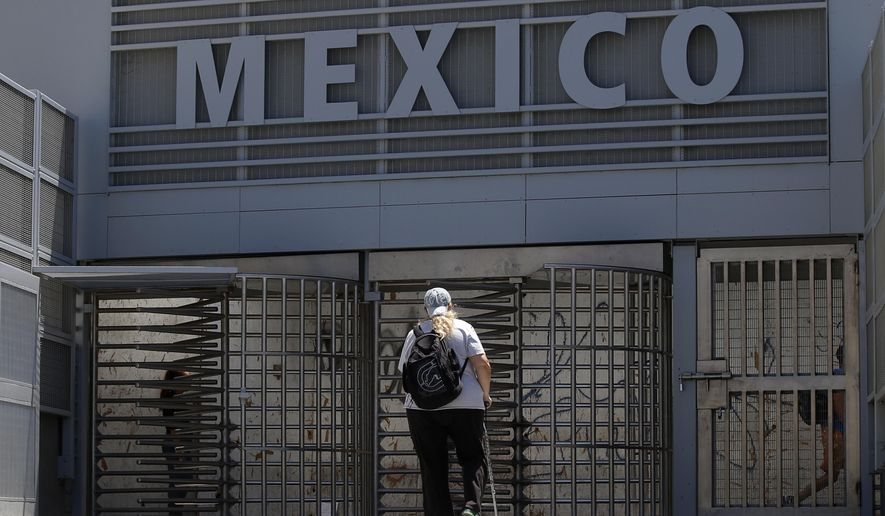 In this Aug. 18, 2015, photo, a woman approaches the entrance to the Mexico border crossing in San Ysidro, Calif. (AP Photo/Lenny Ignelzi) ** FILE **