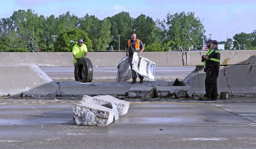 Work crews clean up the scene of a gas tanker fire that was headed south on I-75 near Melvindale, Mich.,  on Thursday, Aug. 20, 2015.  A preliminary investigation found the 53-year-old driver of a truck containing about 8,000 gallons of gasoline was heading southbound on Interstate 75 when he lost control, hitting the median wall and coming to rest in the northbound lanes. Lt. Mike Shaw says fire crews had the flames out about two hours later. The driver was taken to a hospital with severe burns.  (Charles V. Tines/Detroit News via AP)  DETROIT FREE PRESS OUT; HUFFINGTON POST OUT; MANDATORY CREDIT