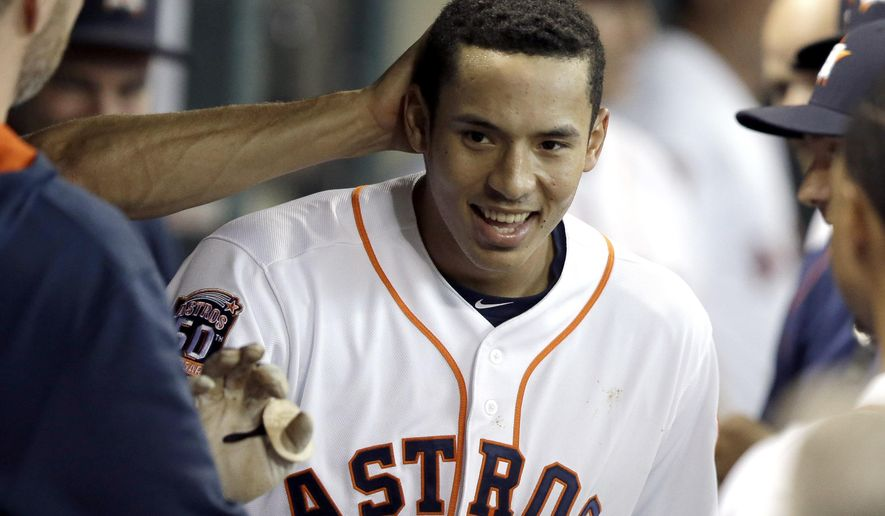 Houston Astros' Carlos Correa is congratulated in the dugout after hitting a solo home run against the Tampa Bay Rays during the first inning of a baseball game Wednesday, Aug. 19, 2015, in Houston. (AP Photo/Pat Sullivan)