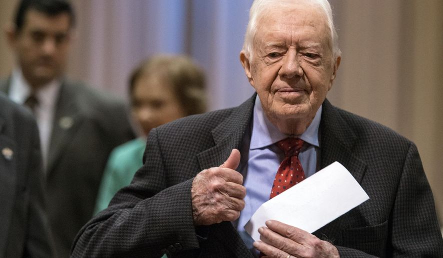 "Former President Jimmy Carter walks to a news conference followed by his wife, Rosalynn Carter, center, at The Carter Center in Atlanta on Thursday, Aug. 20, 2015. Carter announced that his cancer is on four small spots on his brain and he will immediately begin radiation treatment, saying he is ""at ease with whatever comes."" (AP Photo/Ron Harris)"