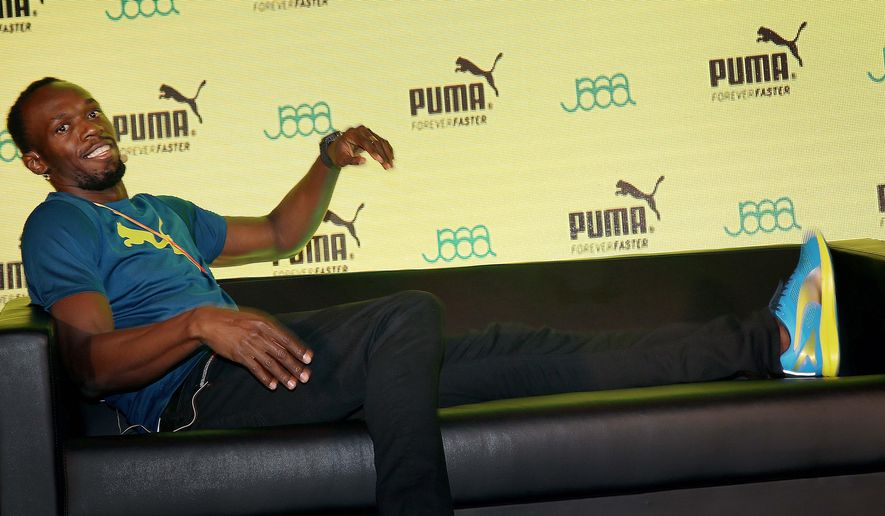 Jamaican sprinter Usain Bolt shares a light moment on stage, with members of the media during a press conference, Thursday, Aug. 20, 2015, in Beijing, China. Bolt will be competing in the upcoming World Athletics Championships in Beijing, where he will look to retain his Men's 100 meter and 200 meter world titles. (AP Photo/Wong Maye-E)