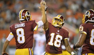 Washington Redskins quarterback Kirk Cousins (8) celebrates his rushing touchdown with wide receiver Reggie Bell (18) during an NFL preseason football game against the Cleveland Browns Thursday, Aug. 13, 2015, in Cleveland. Washington won 20-17. (AP Photo/David Richard)