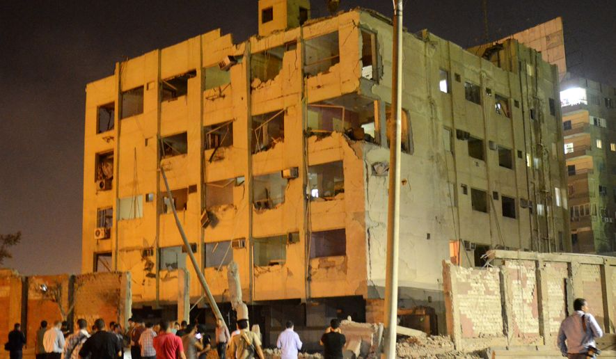 People gather near the scene where a bomb exploded early Thursday, Aug. 20, 2015, near a national security building in the Shubra el-Kheima neighborhood of Cairo. For blocks around the blast site in the popular residential neighborhood, glass from blown-out windows could be seen on the street. (AP Photo/Brian Rohan)